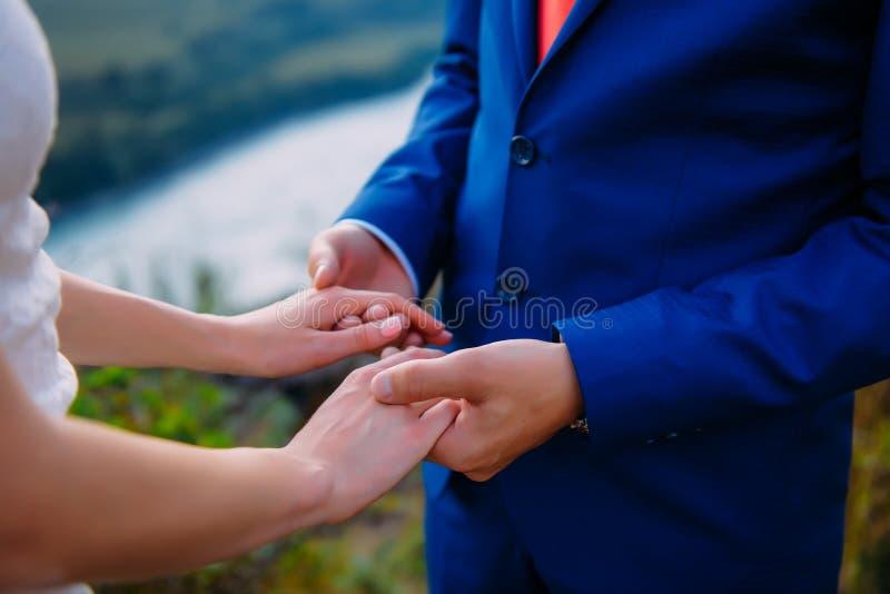 Tema di nozze, tenentesi per mano le persone appena sposate immagini stock