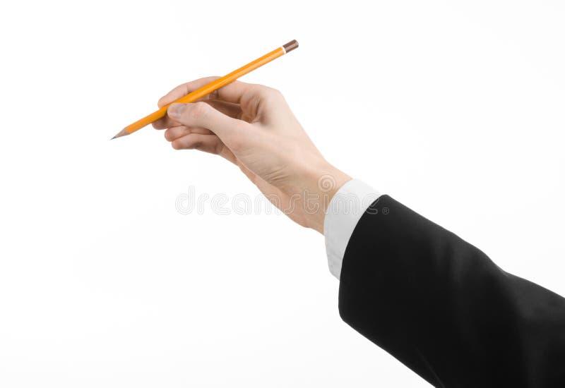 Tema di progettazione e di disegno: la mano dell'artista in un vestito nero che giudica una matita isolata su fondo bianco in stu fotografie stock libere da diritti