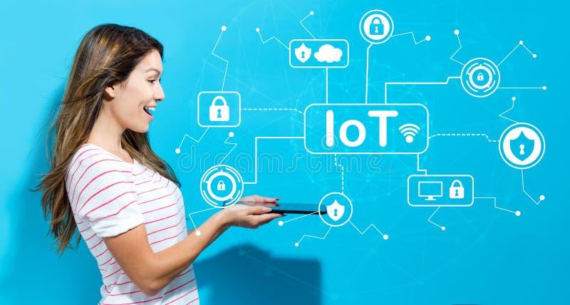 Tema di sicurezza di IoT con la giovane donna che per mezzo della compressa immagini stock libere da diritti