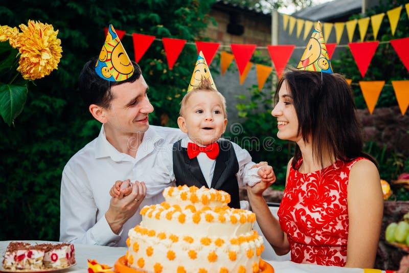 Tema do aniversário das crianças família de três povos caucasianos que sentam-se no quintal da casa em uma tabela decorada festiv fotografia de stock