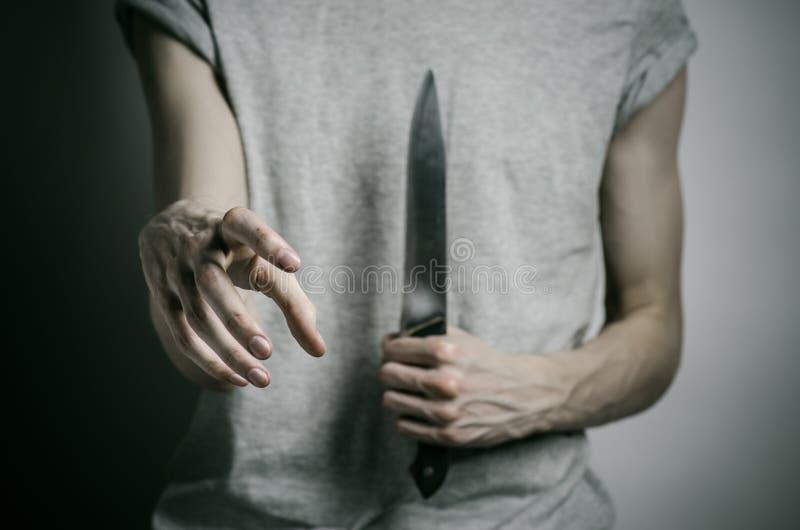 Tema do assassinato e do Dia das Bruxas: um homem que guarda uma faca em um fundo cinzento foto de stock