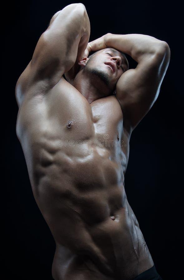 Tema do halterofilista e da tira: bonito com o homem despido bombeado dos músculos que levanta no estúdio em um fundo escuro fotografia de stock