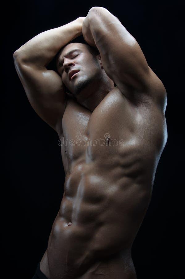 Tema do halterofilista e da tira: bonito com o homem despido bombeado dos músculos que levanta no estúdio em um fundo escuro imagens de stock
