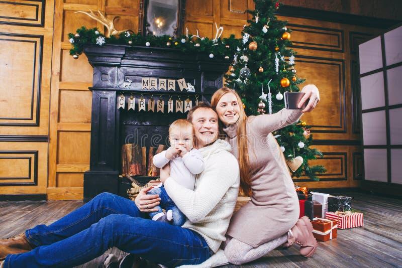 Tema do Natal a família nova com o menino louro de um ano senta-se no assoalho de madeira contra o fundo de uma árvore de Natal c imagens de stock