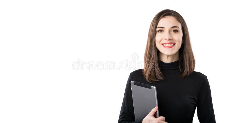 Tema f?r kvinnaaff?rsteknologi H?rlig ung caucasian kvinna i den svarta skjortan som poserar p? anseende med minnestavlah?nder royaltyfria bilder