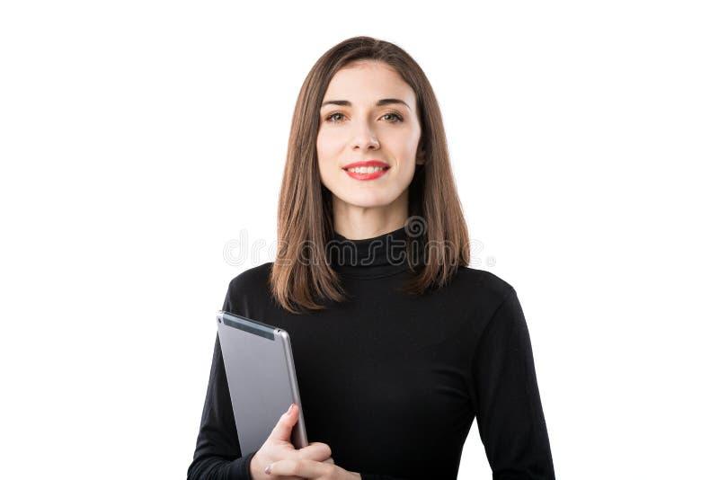 Tema f?r kvinnaaff?rsteknologi H?rlig ung caucasian kvinna i den svarta skjortan som poserar p? anseende med minnestavlah?nder royaltyfri fotografi