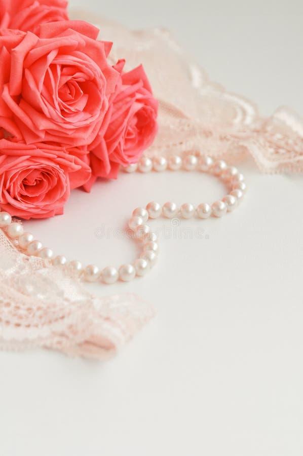 Tema feminino delicado As rosas corais cor-de-rosa tendem a cor em um pálido - colar cor-de-rosa do sutiã e da pérola em um fundo fotos de stock