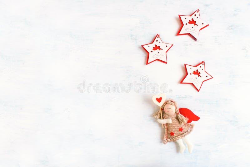Tema festivo di festa di Natale con l'angelo del giocattolo e la stella bianca rossa tre fotografia stock