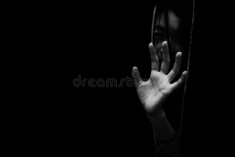 Tema a la muchacha que oculta en armario con la mano que alcanza hacia fuera foto de archivo