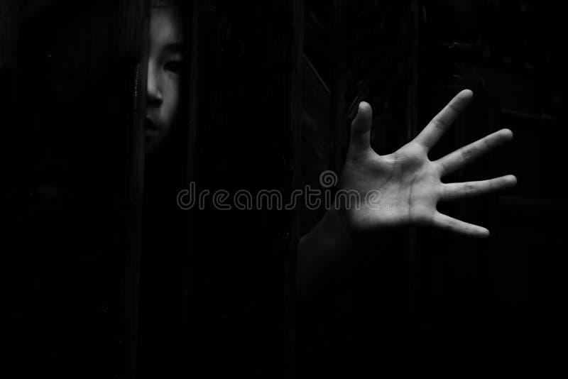 Tema a la muchacha que oculta en armario con la mano que alcanza hacia fuera imagenes de archivo