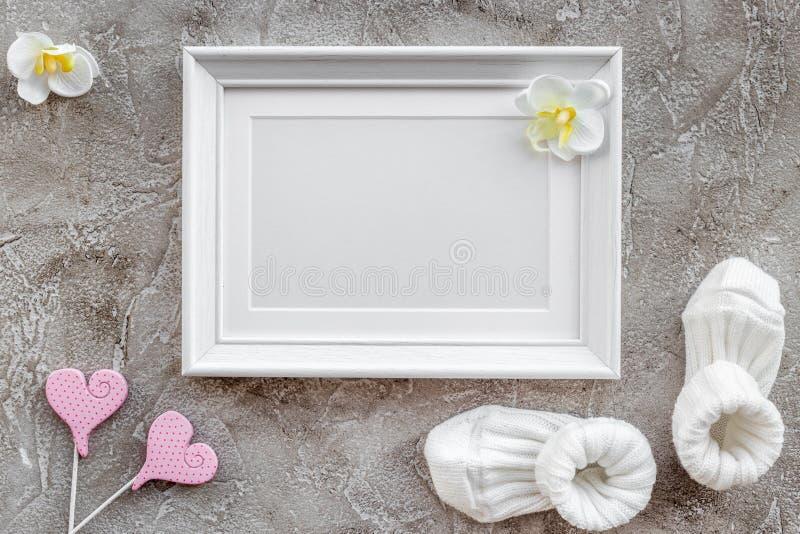 Tema para a festa do bebê com sapatas e espaço cinzento da opinião superior do fundo do quadro branco para o texto fotografia de stock