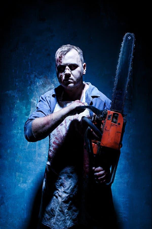 Tema sanguinoso di Halloween: uccisore pazzo come macellaio con la sega elettrica fotografia stock libera da diritti
