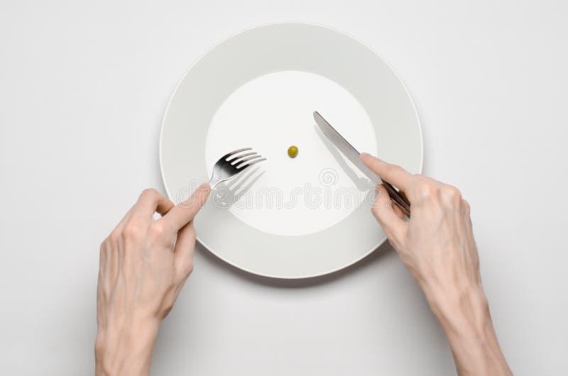 Tema saudável do alimento: mãos que guardam a faca e a forquilha em uma placa com ervilhas verdes em uma opinião de tampo da mesa foto de stock royalty free