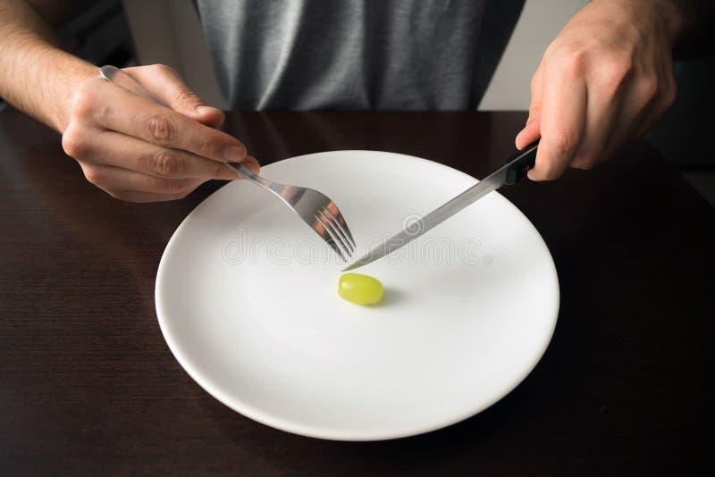 Tema saudável do alimento: mãos que guardam a faca e a forquilha em uma placa com uva verde em uma placa branca fotos de stock royalty free