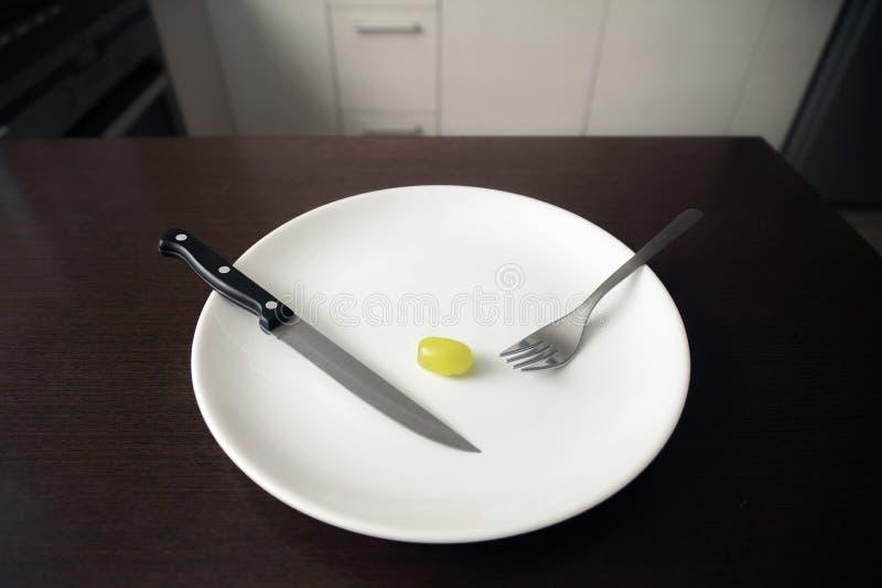Tema saudável do alimento: uva verde em uma placa branca afrouxando o peso, estilo de vida saudável imagens de stock