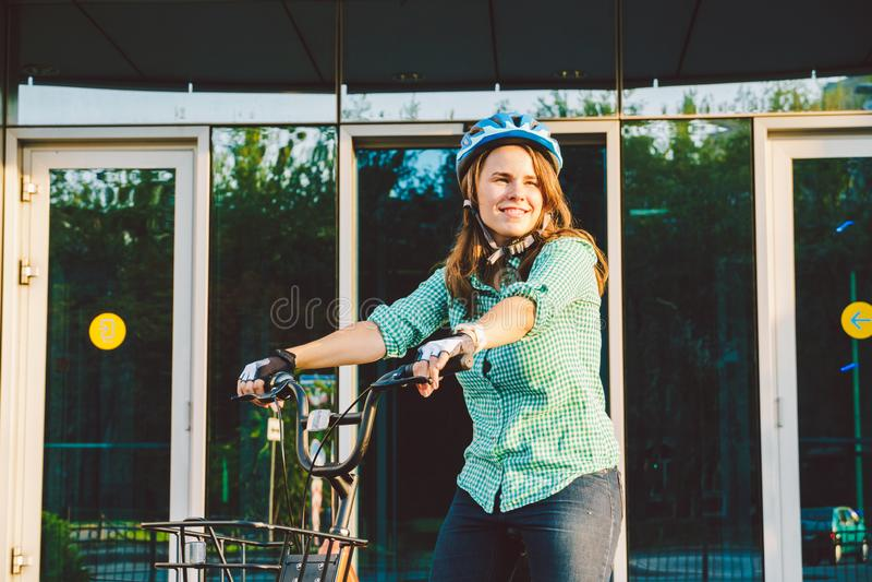 Tema som arbetar på cykeln En ung Caucasian kvinna ankom på den miljövänliga transportcykeln till kontoret Flicka i en bic fotografering för bildbyråer