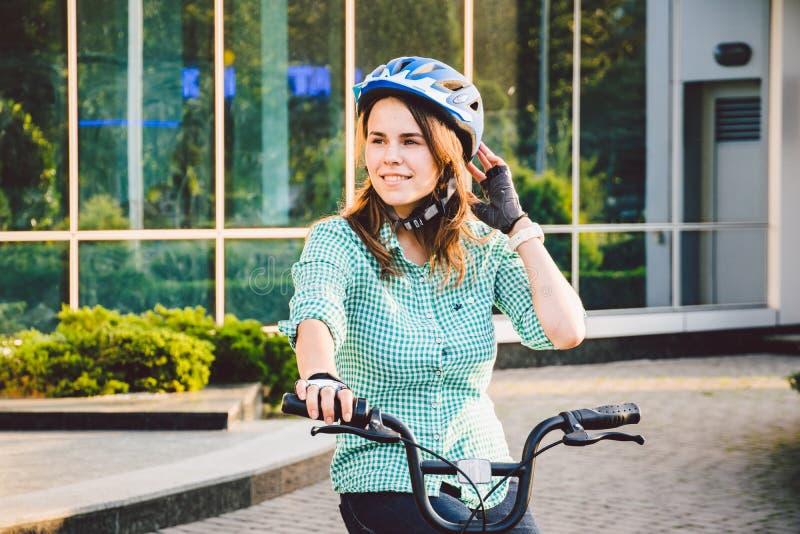 Tema som arbetar på cykeln En ung Caucasian kvinna ankom på den miljövänliga transportcykeln till kontoret Flicka i en bic arkivbild