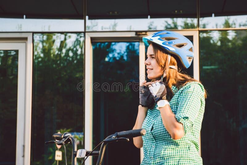 Tema som arbetar p? cykeln En ung Caucasian kvinna ankom p? den milj?v?nliga transportcykeln till kontoret Flicka i a royaltyfria foton