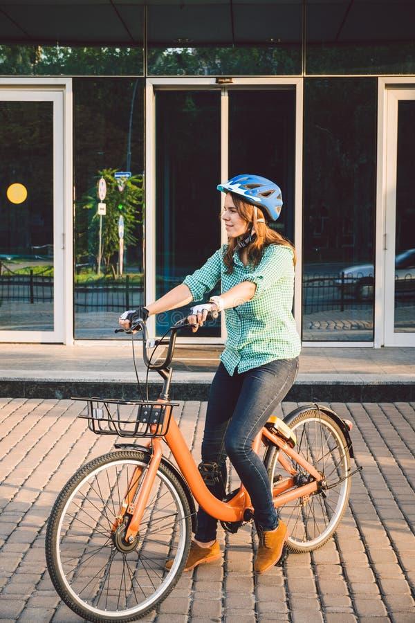 Tema som arbetar p? cykeln En ung Caucasian kvinna ankom p? den milj?v?nliga transportcykeln till kontoret Flicka i a arkivbilder