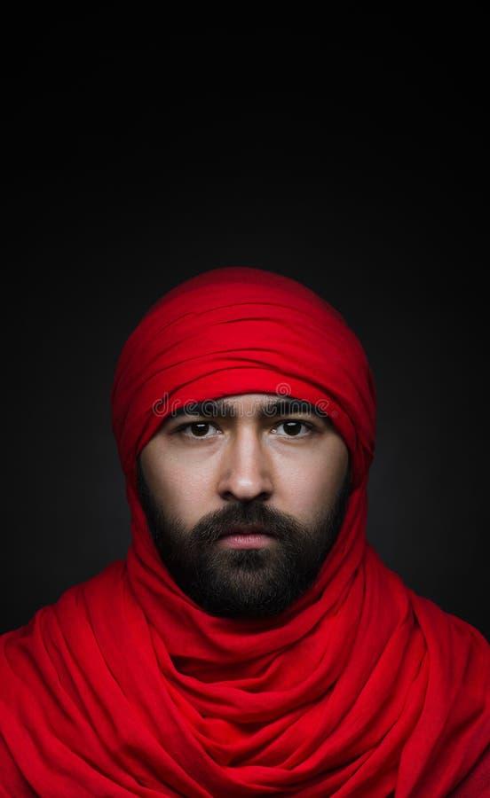 Tema turco ed arabo: bello uomo musulmano con una barba in un foulard rosso isolato su un fondo nero in studio fotografie stock libere da diritti