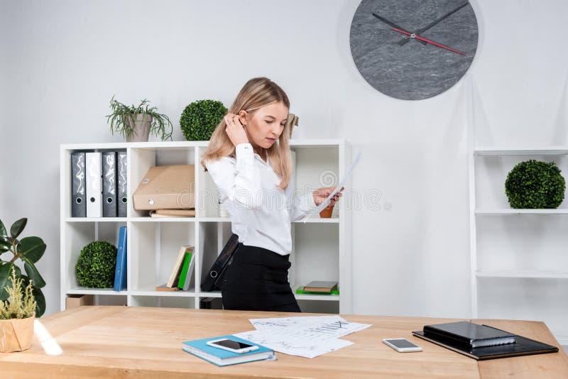 Temaaffärskvinna på arbete Härligt ungt caucasian arbetande anseende för kvinnaaffärsman i kontoret nära tabellen, kontroller royaltyfri fotografi