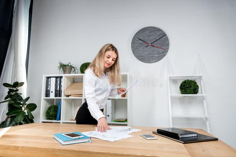 Temaaffärskvinna på arbete Härligt ungt caucasian arbetande anseende för kvinnaaffärsman i kontoret nära tabellen, kontroller royaltyfri foto