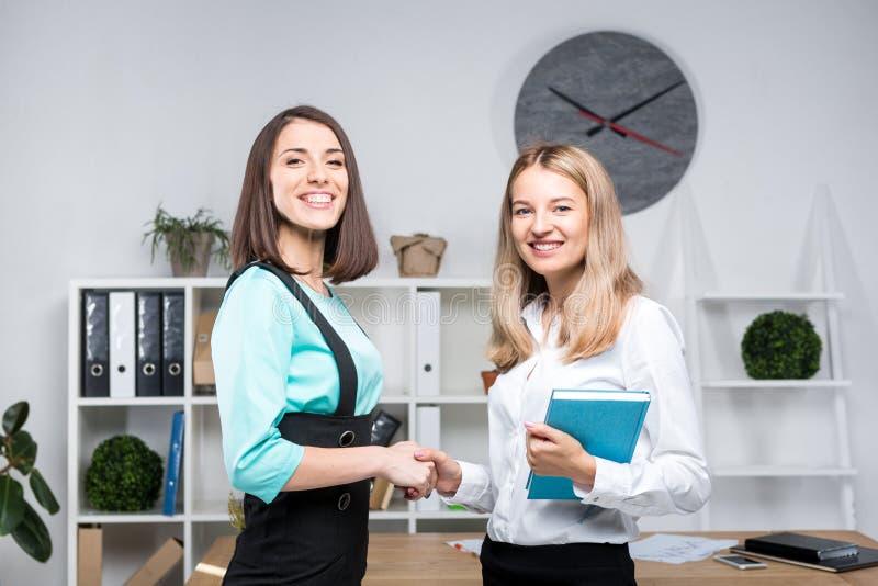 Temaaffärskvinnor Två unga Caucasian kvinnaaffärspartners i formell kläder undertecknar ett avtal som in gör ett avtal en handska royaltyfria bilder
