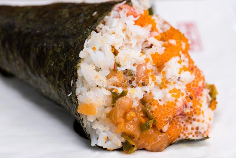 Temaki norihavsväxtkotte som stoppas med ris, laxen och kaviaren som medföljs av wasabi och gari royaltyfri fotografi