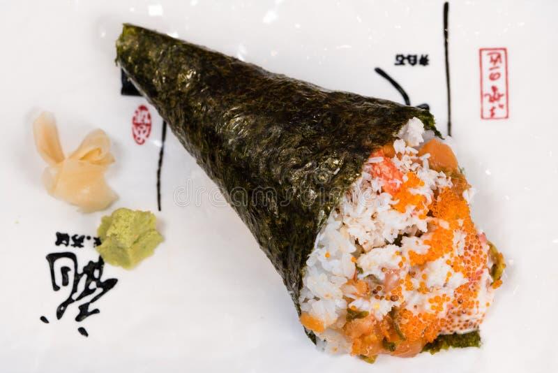 Temaki norihavsv?xtkotte som stoppas med ris, laxen och kaviaren som medf?ljs av wasabi och gari arkivfoto