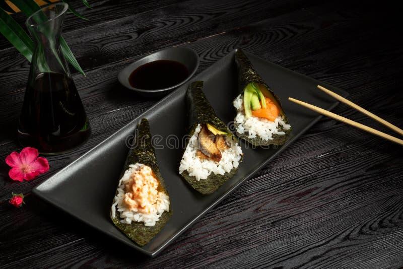 Temakimengeling met zalm, paling en garnalen op een donkere houten achtergrond stock afbeeldingen