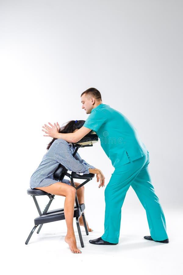 Temamassage och kontor Manlig terapeut med den blåa dräkten som gör baksida- och halsmassagen för arbetare för ung kvinna, affär royaltyfri foto