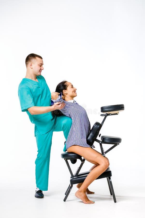 Temamassage och kontor ung manlig terapeut i blåttdräkten som tillbaka gör massage med hans knä som stödjs i ryggen av den kvinnl arkivfoton
