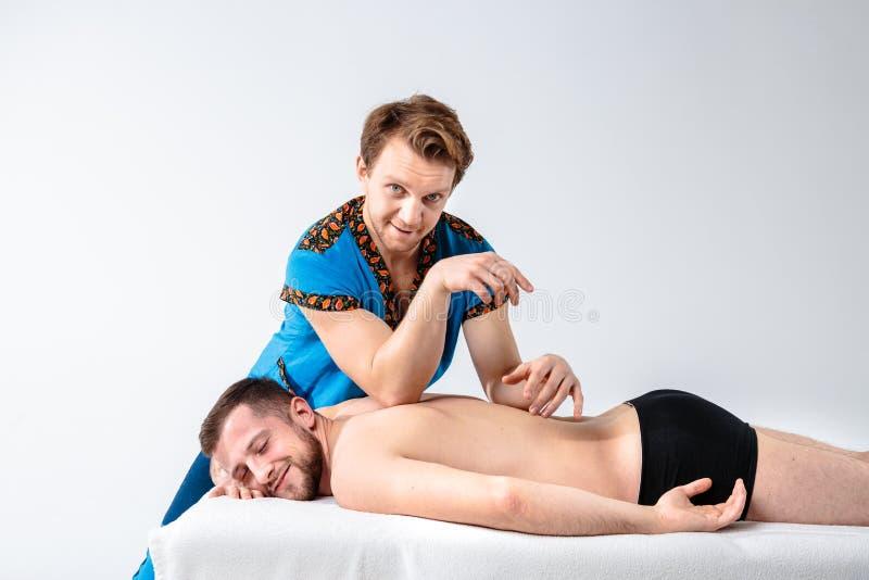 Temamassage och kroppomsorg Den härliga caucasian mannen i blå likformig och skägget som gör sträckning, läker, diagnosen av till royaltyfri foto