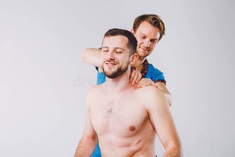 Temamassage och kroppomsorg En stilig Caucasian manlig doktor i blått likformig och skägg som diagnostiserar muskler av halsen oc arkivfoton