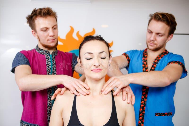 Temamedicin och rehabilitering behandlar den unga manliga doktorsmassören för två tvilling- bröder att massera en ung kvinna på e royaltyfria foton