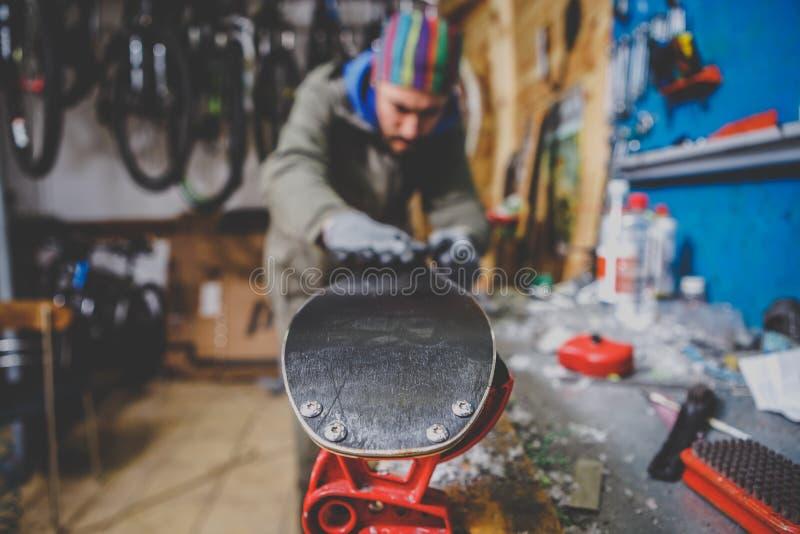 Temareparationer och underhåll av skidar Den manliga arbetaren reparerar arbetskläder som applicerar vaxet på glidningsyttersidan royaltyfri fotografi