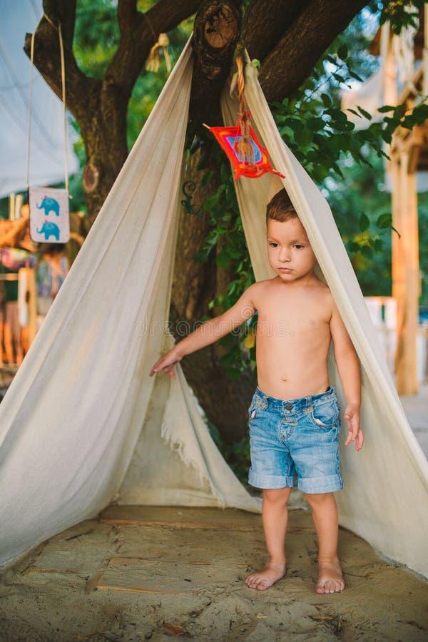 Temasommarsemestern, pys, parkerar det Caucasian barnet som spelar i skogsbevuxet område i, på lekplats i gård unge i tipivigvamt royaltyfri foto