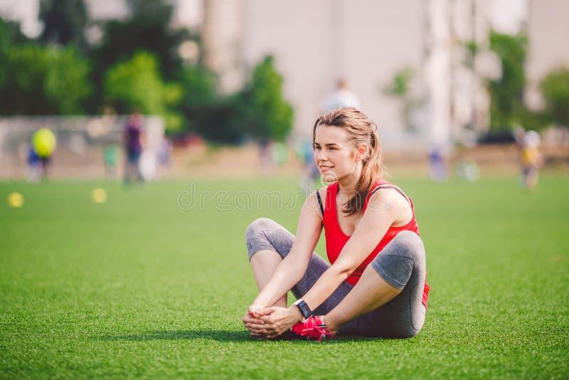 Temasport och hälsa Ung härlig Caucasian kvinna som sitter göra uppvärmning och att värma muskler som upp sträcker grönt gräs arkivbild