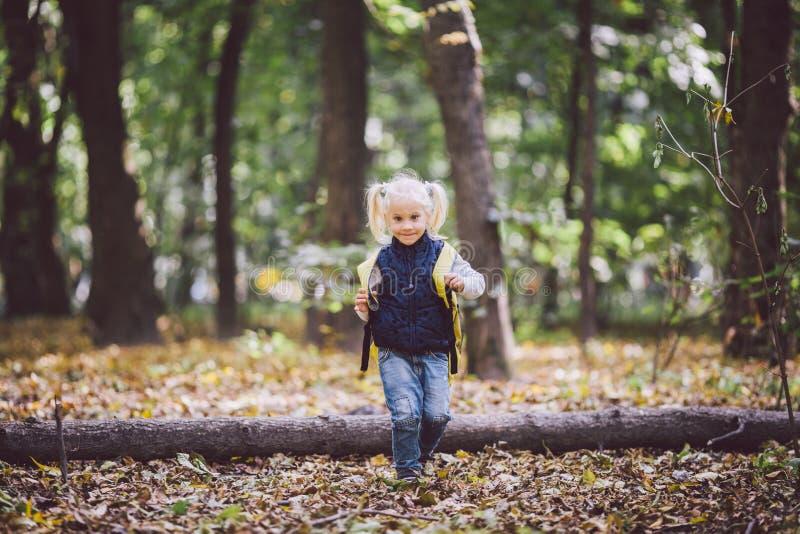 Tematów dzieci plenerowe aktywność Śmieszny mały dziecko spadał Kaukaska blond dziewczyna chodzi przez lasowych pokonywanie przes zdjęcie royalty free