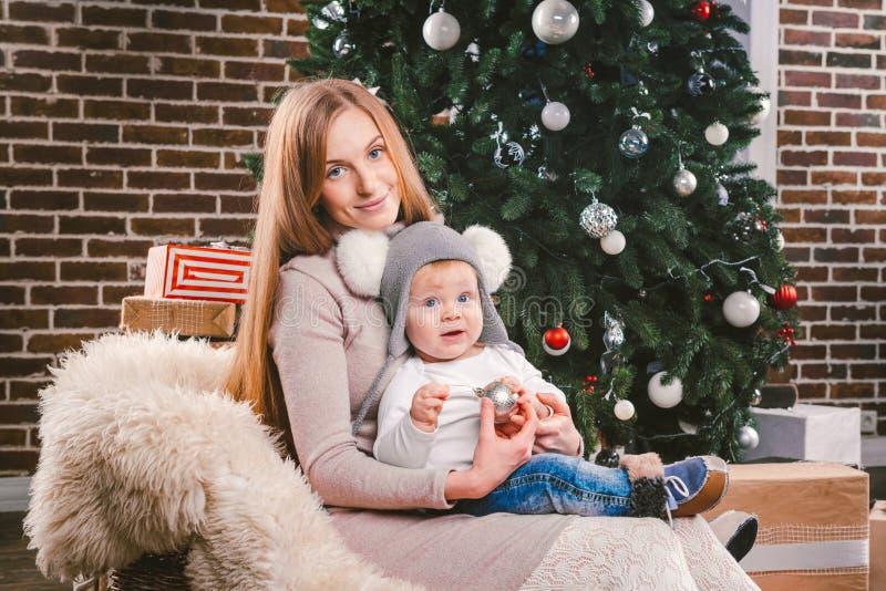 Tematów wakacji zimy Bożenarodzeniowy nowy rok Młoda elegancka Kaukaska matka trzyma jej syna w jej rękach dla 1 roku w śmiesznej fotografia stock