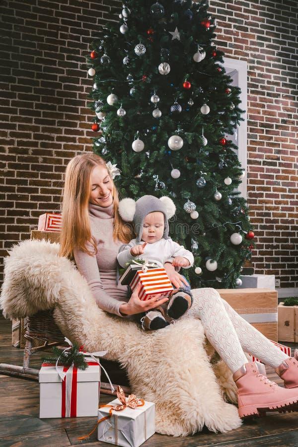 Tematów wakacji zimy Bożenarodzeniowy nowy rok Młoda elegancka Kaukaska matka trzyma jej syna w jej rękach dla 1 roku w śmiesznej obraz royalty free