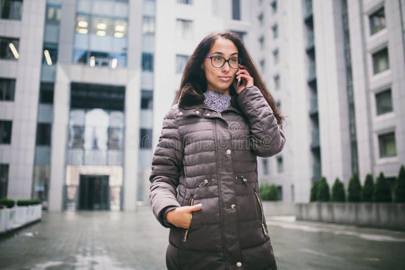 Temat är affärsläget Härlig ung kvinna av europeisk etnicitet med exponeringsglas och laget för långt brunetthår det stan bärande fotografering för bildbyråer