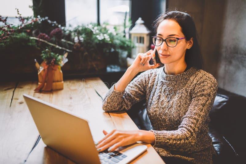 Temat är små och medelstora företag En ung frilans- kvinna som arbetar bak en bärbar datordator i en coffee shop, dekorerade med  royaltyfria foton