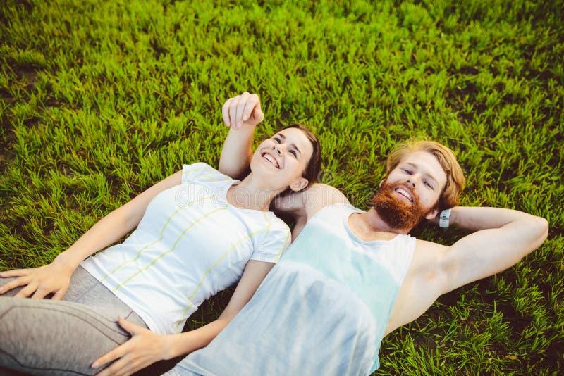 Temat är sporten och en sund livsstil Ung ett man- och kvinnapar vilar att ligga på deras baksidor på det gröna gräset, en gräsma royaltyfri foto