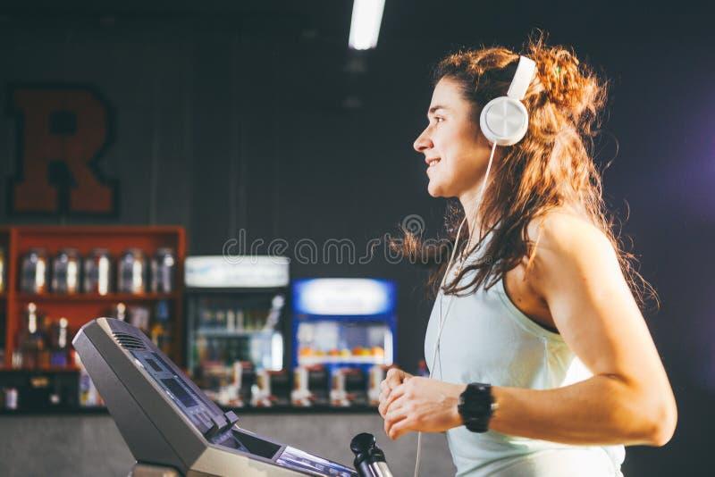 Temat är sporten och musik En härlig uppblåst kvinna kör i idrottshallen på en trampkvarn På hennes huvud är den stora vita hörlu arkivbild