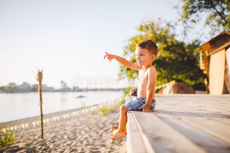 Temat jest dziecka i lato plaży wakacje Mała Kaukaska chłopiec siedzi z ukosa na drewnianym molu i pokazuje jego rękę na piaskowa obrazy royalty free