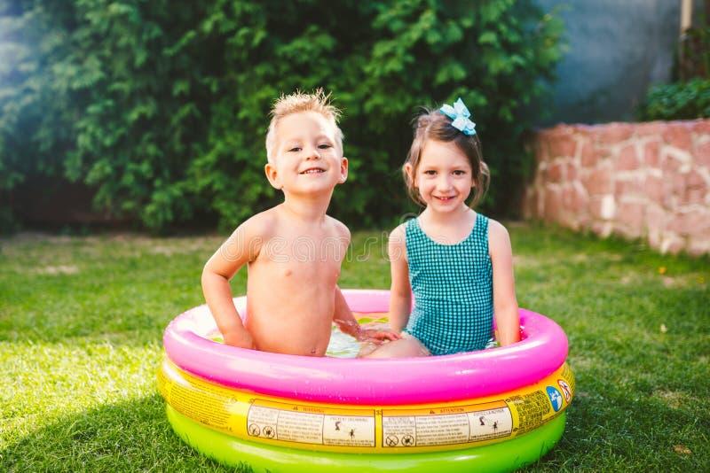 Temat jest dziecka wakacje Dwa Kaukaskiego dziecka brat i siostra, siedzą w umieszczam wokoło basenu z wodą w zdjęcia stock
