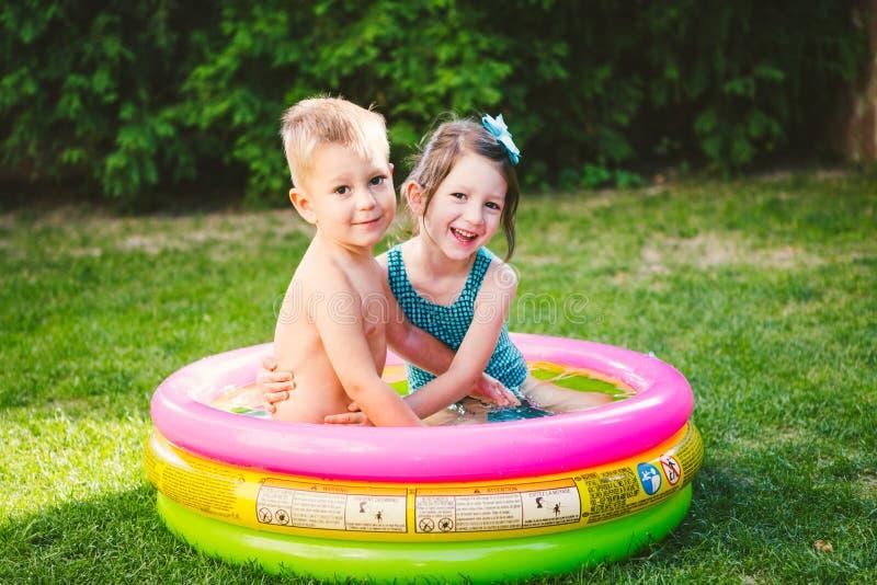 Temat jest dziecka wakacje Dwa Kaukaskiego dziecka brat i siostra, siedzą w umieszczam wokoło basenu z wodą w obrazy royalty free