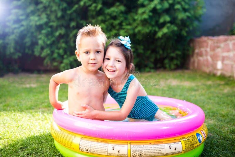Temat jest dziecka wakacje Dwa Kaukaskiego dziecka brat i siostra, siedzą w umieszczam wokoło basenu z wodą w fotografia stock