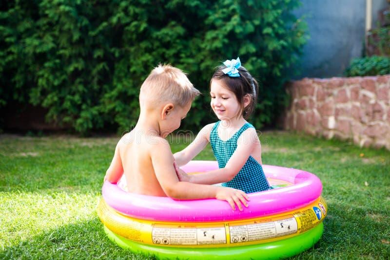 Temat jest dziecka wakacje Dwa Kaukaskiego dziecka brat i siostra, siedzą w umieszczam wokoło basenu z wodą w obrazy stock